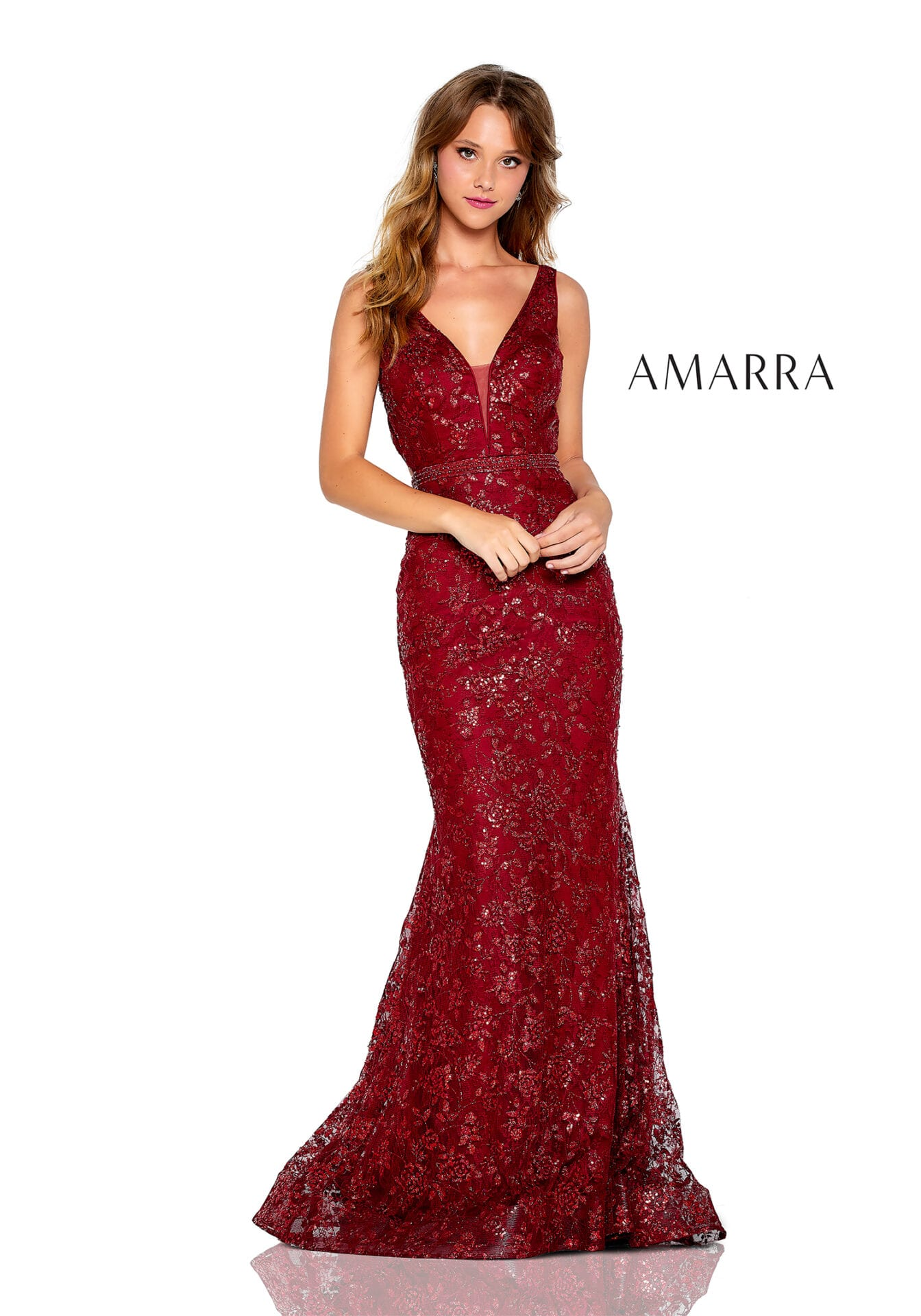 Fitted gown featuring a V-neck with mesh insert, beaded belt, and glitter sequin floral pattern.