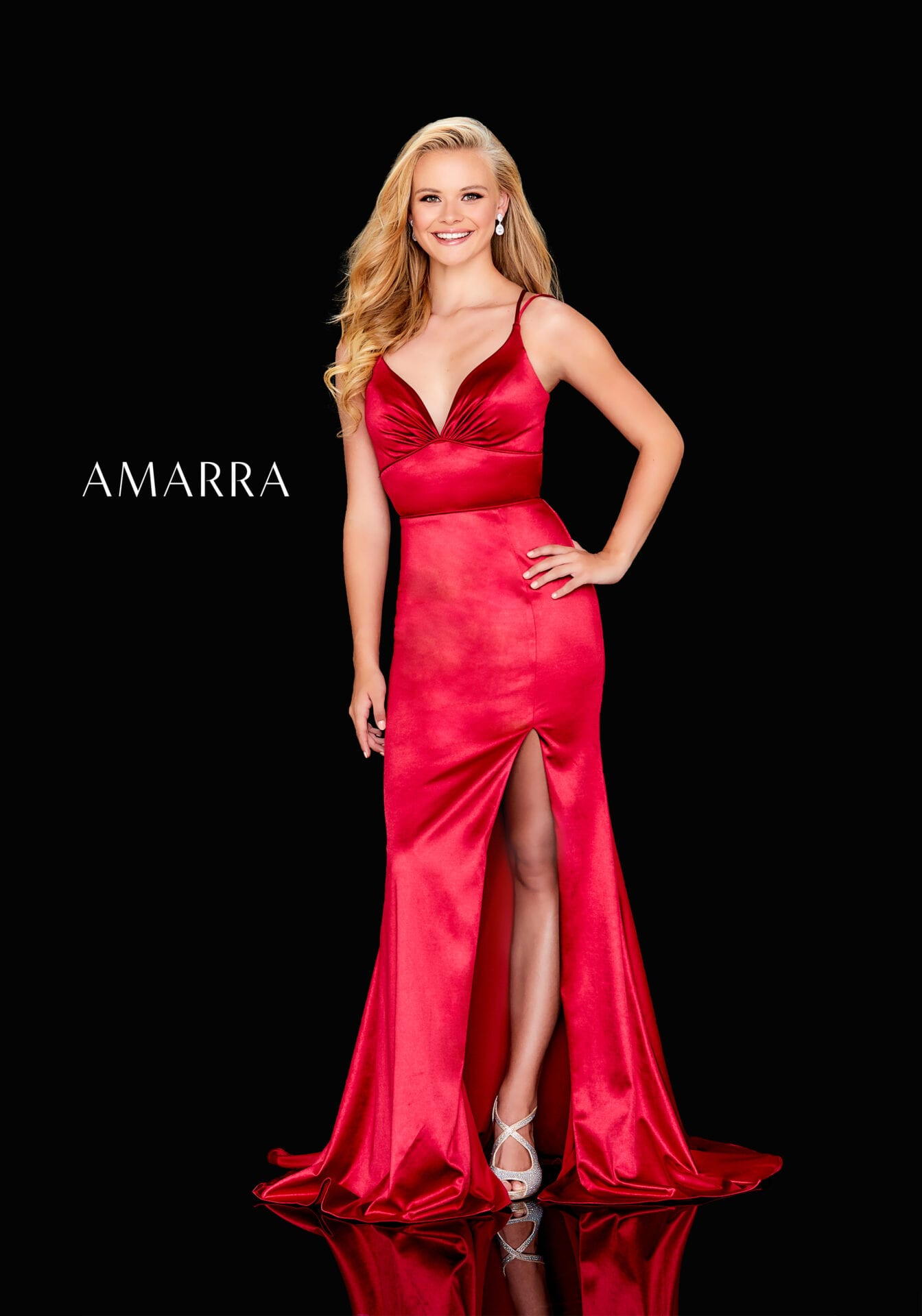 Stretch satin gown featuring ruched top, double straps, lace up back, ruched bottom, and slit skirt.