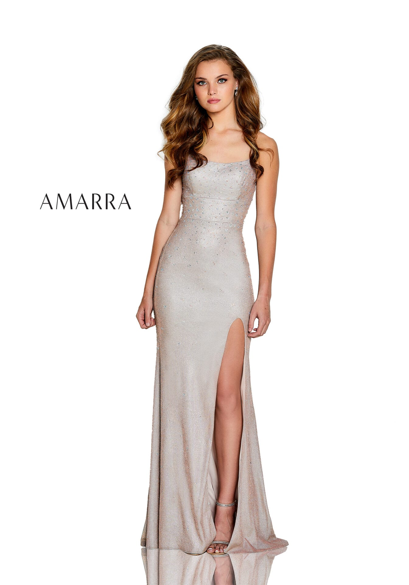 Fitted shimmer gown featuring a scoop neckline, flared beading that gradually cascades down, slit skirt, and lace up back.