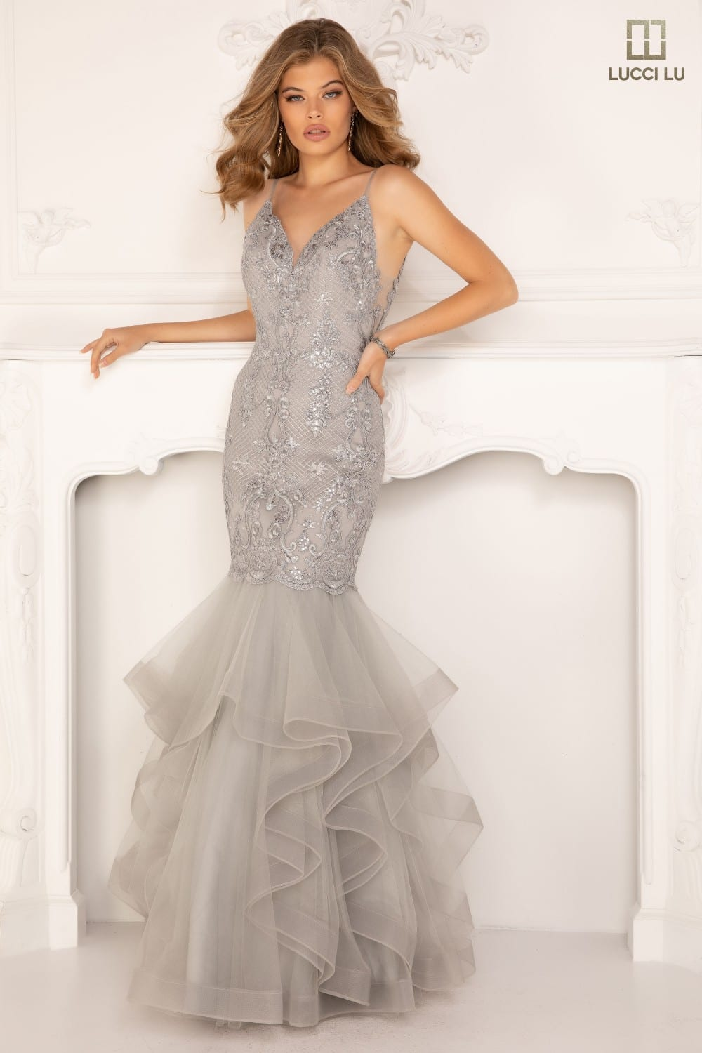 Mermaid gown with a v-neck bodice, beaded embroidery, spaghetti straps, open back, illusion sides, and tulle ruffles with a horsehair hem.